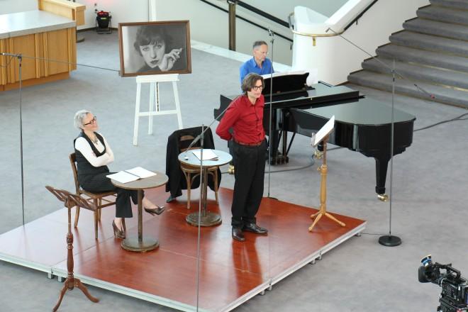 eine Frau am Tisch sitzend, ein Mann und ein zweiter Mann am Klavier