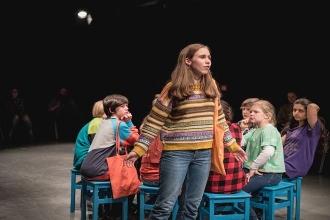 ein Mädchen im Vordergrund und im Hintergrund sitzen Jungen und Mädchen