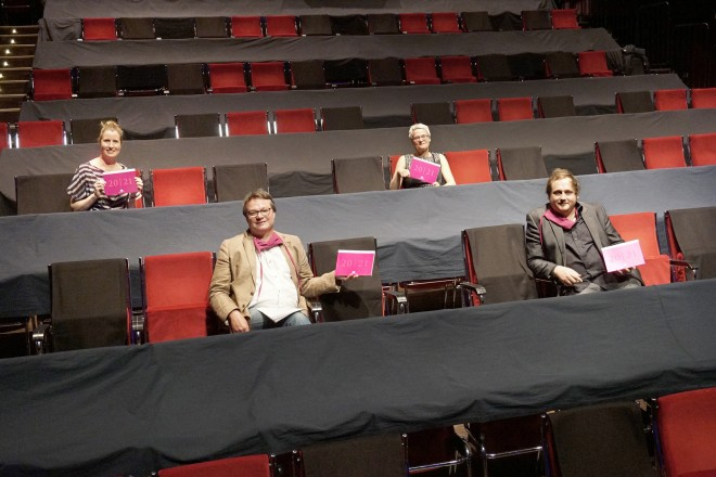 vier Personen sitzend im Theatersaal