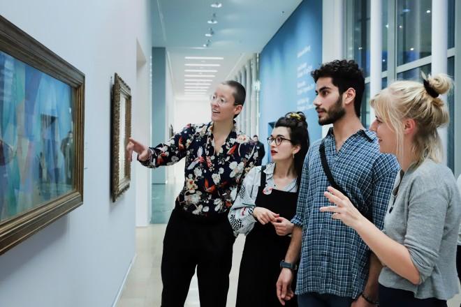 vier Personen betrachten ein Gemälde