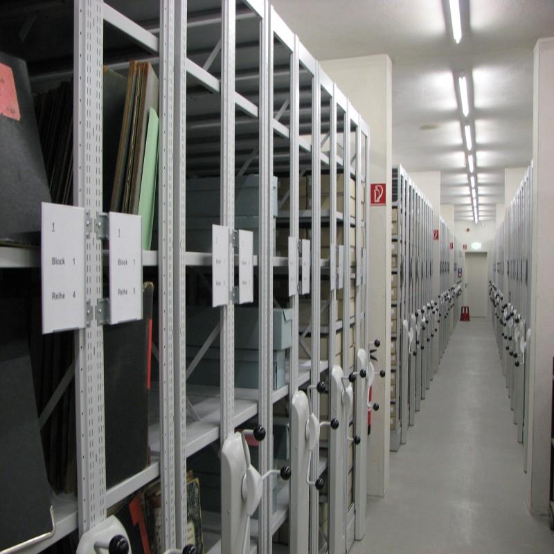 Foto: Blick auf eine mit Unterlagen gefüllte Rollregalanlage im Archivmagazin
