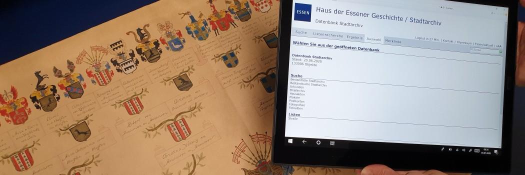 Foto: Tablet mit geöffneter Datenbank vor einer historischen Stammtafel