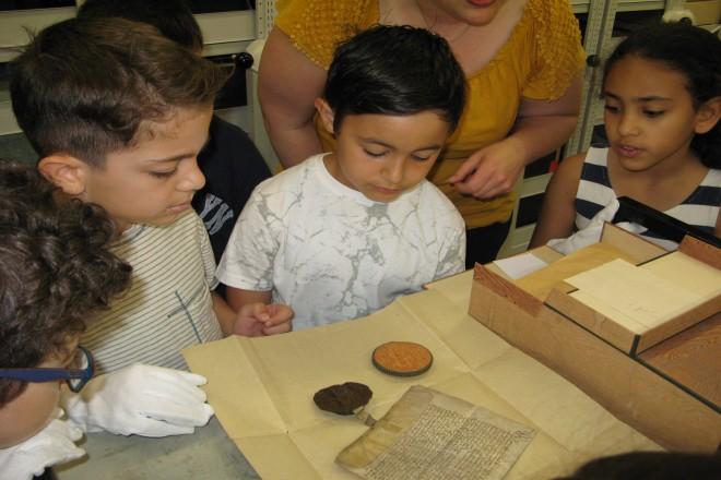 Foto: Grundschülerinnen und Grundschüler betrachten unter Anleitung konzentriert eine Original-Urkunde aus dem Jahr 1576