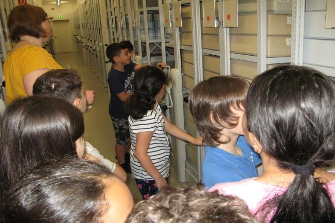 Foto: Kinder im Grundschulalter drehen im Magazin des Stadtarchivs an einer Rollregalanlage