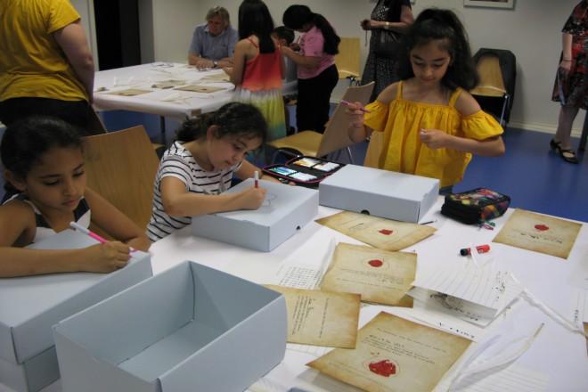 Foto: Eine Gruppe von Grundschülern erstellt mithilfe von Tinte, Schreibfedern und Wachs eigene Urkunden.