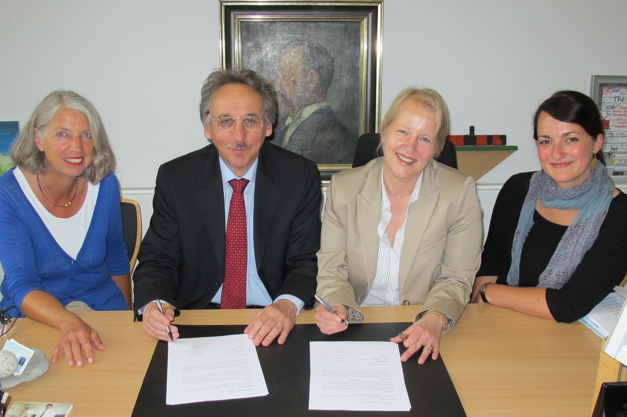 Vier Personen sitzen am Tisch, um eine Vereinbarung zu unterzeichnen