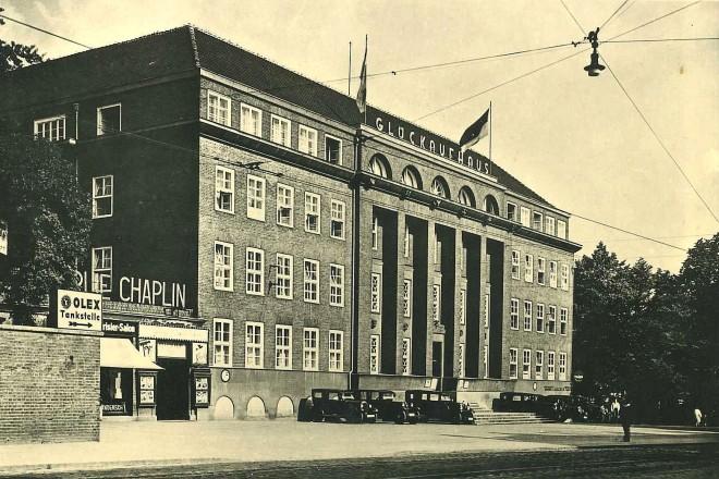 """Foto: Haupteingang des Glückaufhauses mit davor parkenden Autos, auf dem Dach der Schriftzug """"Glückaufhaus"""", links daneben Kinowerbung mit dem Schriftzug """"Chaplin"""""""