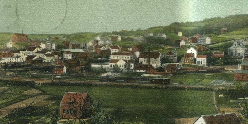 Historische Postkarte: Blick auf die Wohnhäuser von Kupferdreh um 1905, im Vordergrund fährt eine Eisenbahn entlang