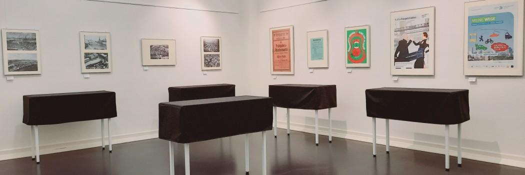 Foto:Foto: Ausstellungsraum Sonderausstellung mit 5 schwarz abgehangenen Vitrinen und 8 ausgestellten Bildern an der Wand