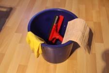 Foto: Ein blauer Putzeimer gefüllt mit Putzutensilien
