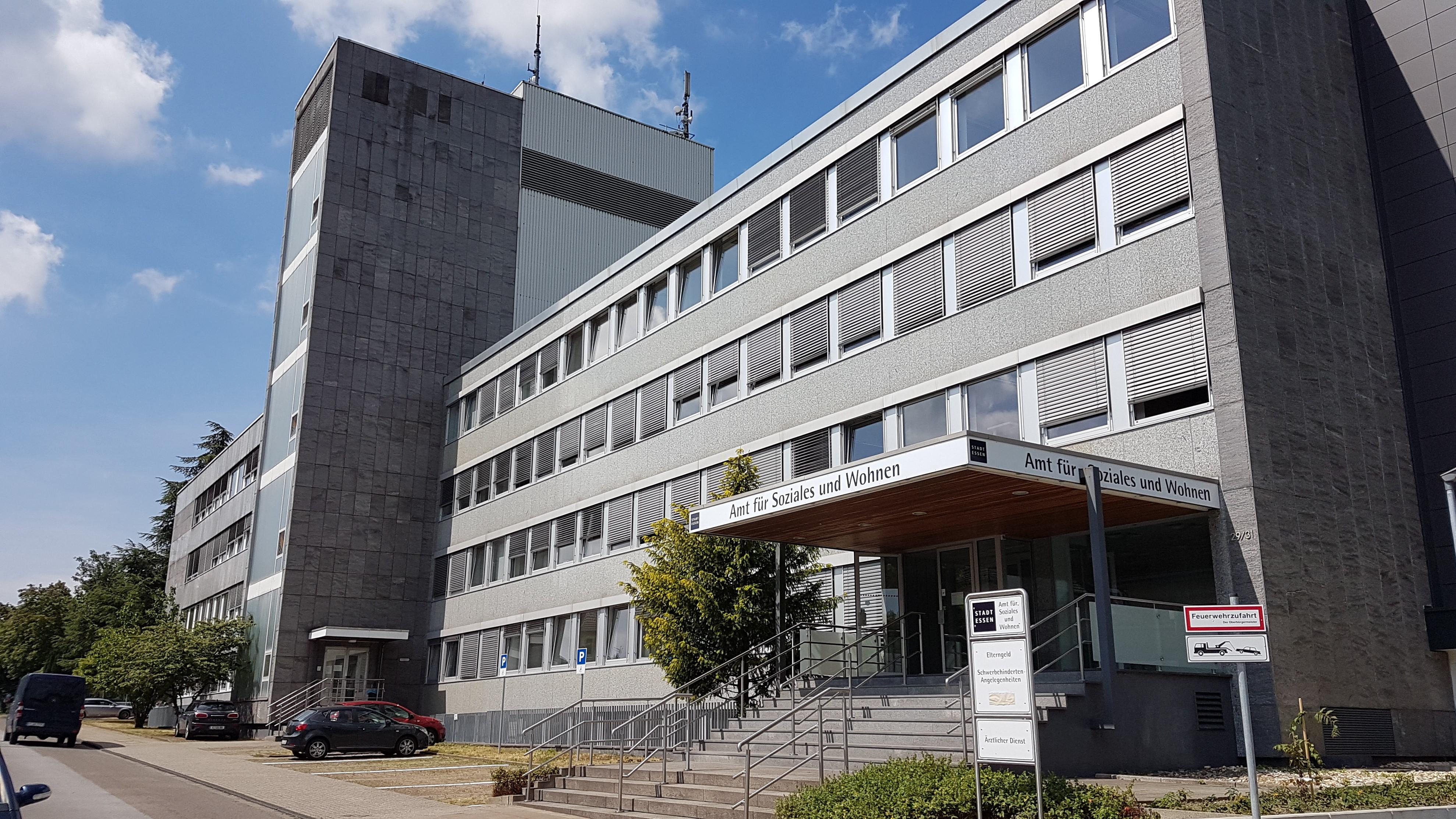 Foto: Eingang des Verwaltungsgebäudes Klinkestr. 29-31, Aufschrift: Amt für Soziales und Wohnen. Ein Schild im Vordergrund Elterngeld und Schwerbehindertenangelegenheiten.