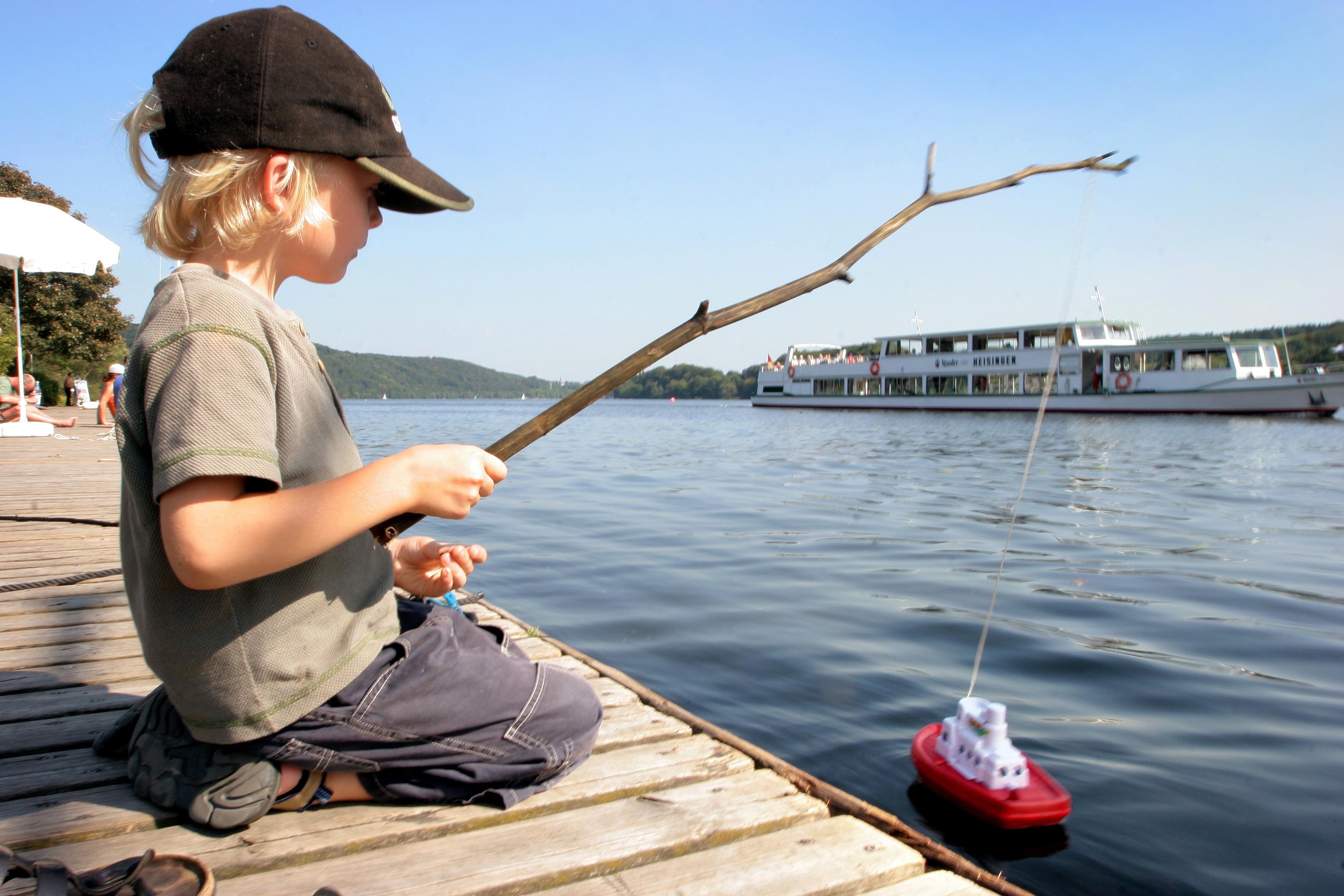 Junge am Baldeneysee mit einem Schiff an einer Holzangel