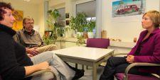 Foto: Zwei Frauen und ein Mann sitzen an einem Tisch und sprechen miteinander