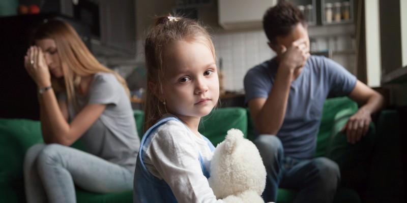 Foto: Kind mit Teddybär zwischen verzweifelten Eltern.