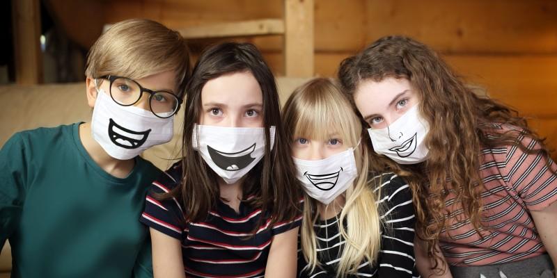 Foto: Kinder mit bemalten Corona-Masken