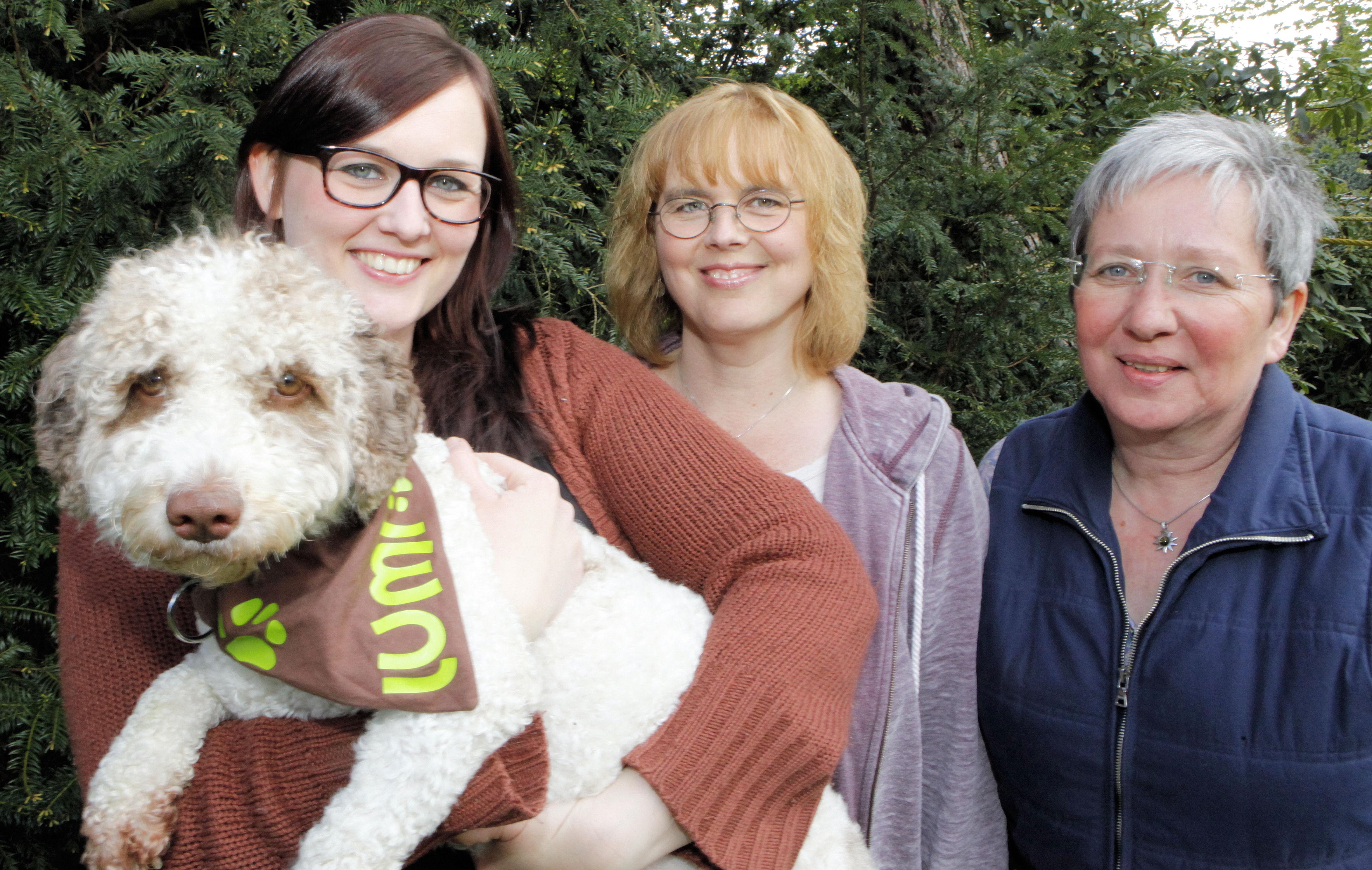 Drei Frauen und ein Hund schauen freundlich