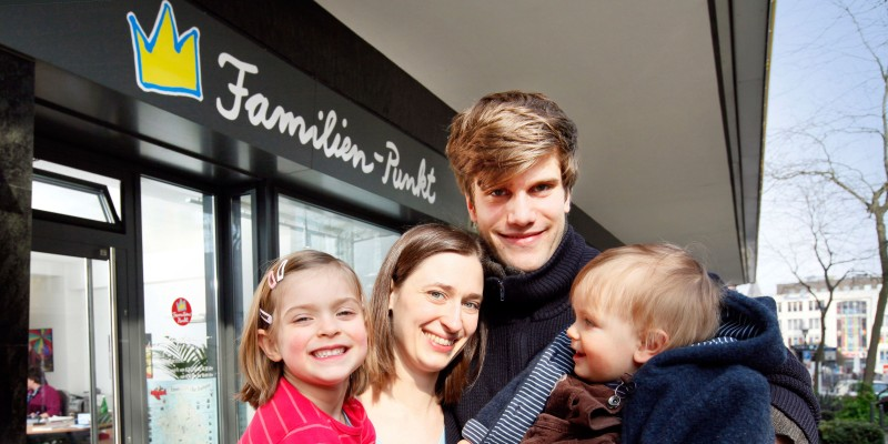 Familie steht vor dem Eingang des Familienpunktes