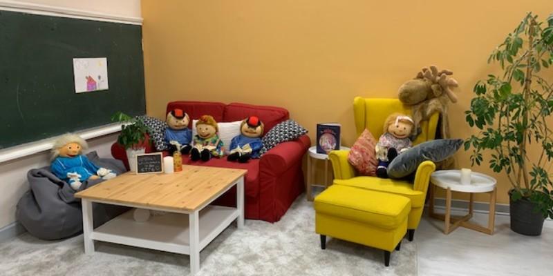 Puppen sitzen auf Sofa und Sessel