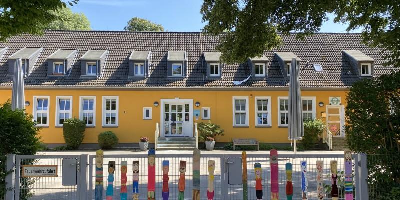 Im Vordergrund des gelben Kitagebäudes ist ein Metallzaun mit vielen bunt bemalten Holzlatten, die Kinder darstellen