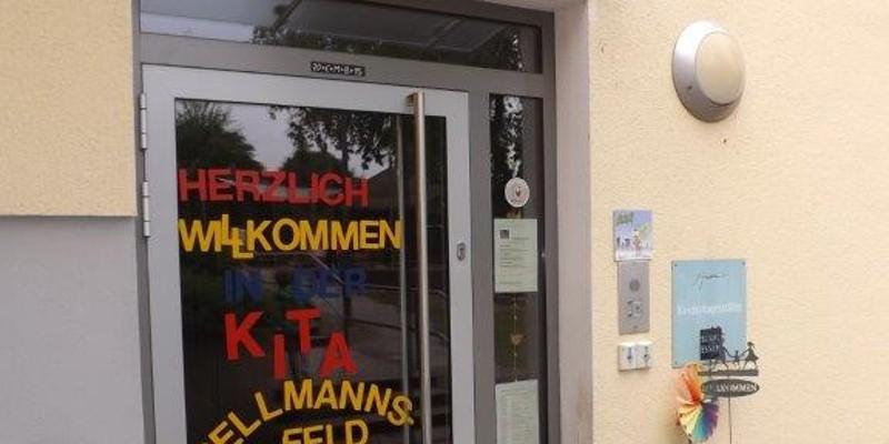 """Gläserne Eingangstür der Kita mit bunter Beschriftung """"Herzlich Willkommen in der Kita Dellmannsfeld"""""""