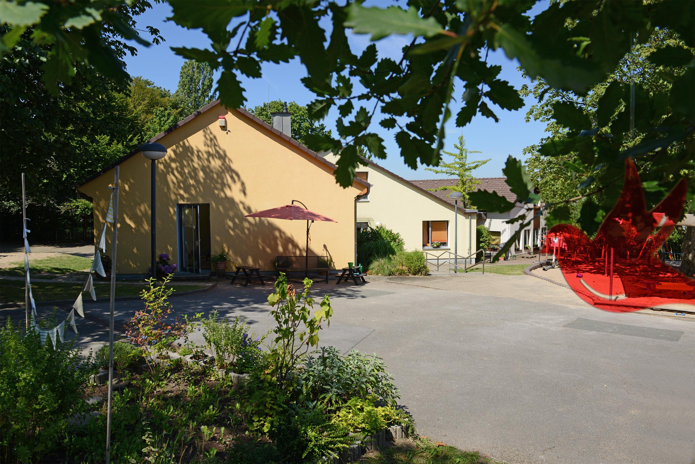 Das Gebäude der Kita Dellmannsfeld und der Außenbereich an einem sonnigen Tag