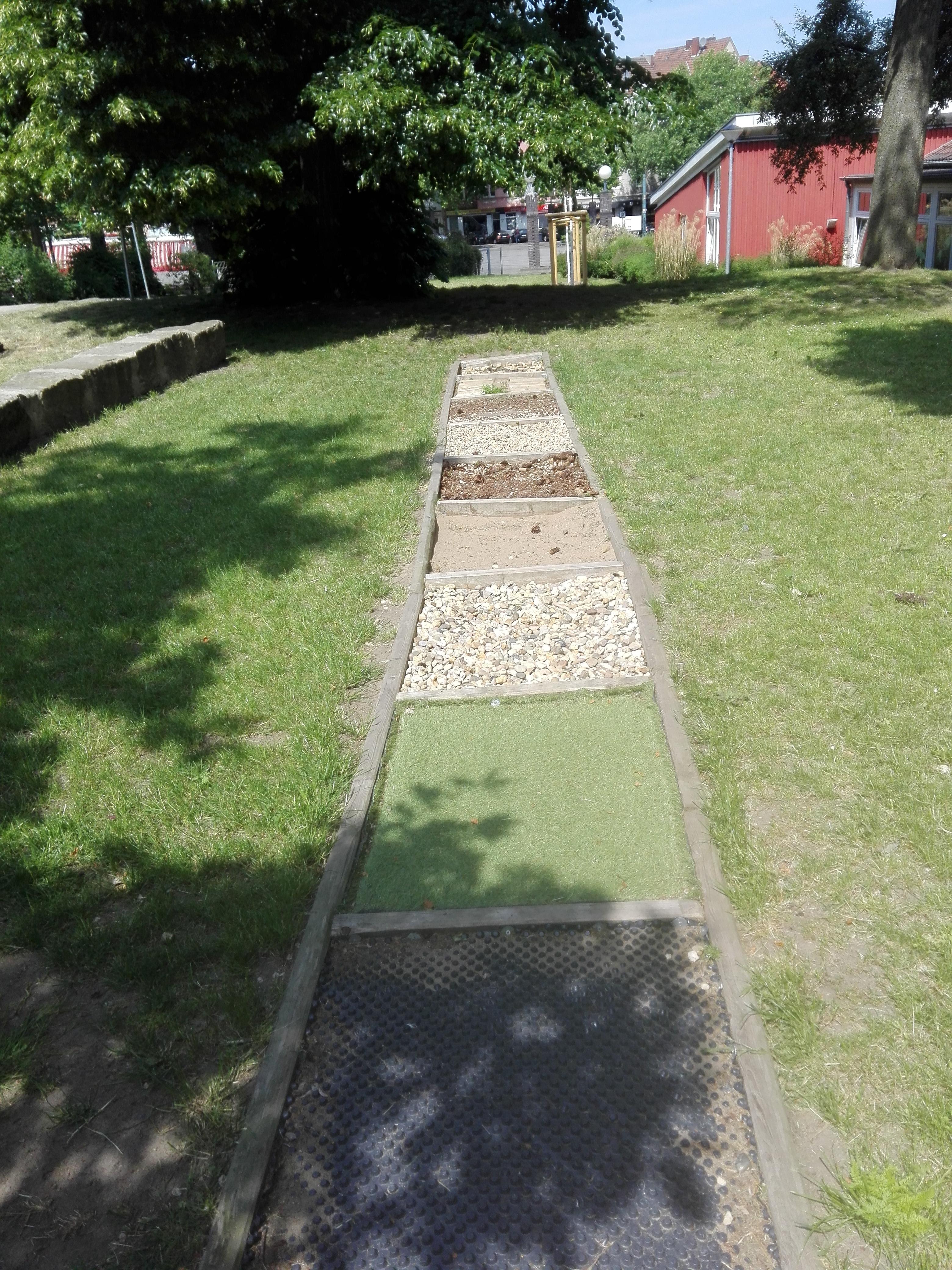 ein eingesäumter Fußweg mit unterschiedlichen Bodenbelegen