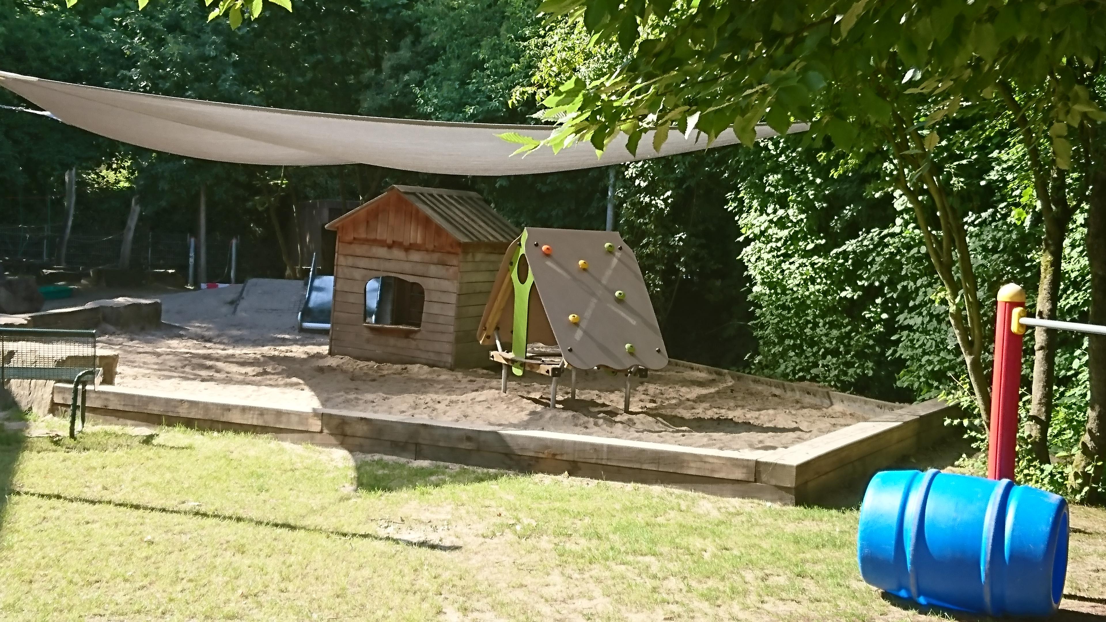 Sandkasten mit Holzhaus und Sonnensegel