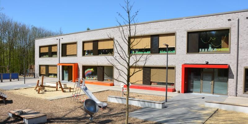 Das Gebäude Kita Raadter Straße mit Blick auf das Außengelände mit Sandkasten und Spielgeräten