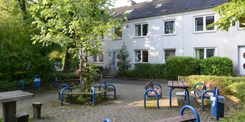 Kitagebäude mit Sitzbänken im Außenbereich mit Bäumen