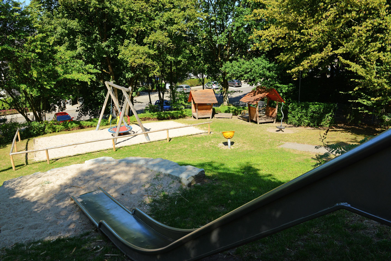 Rutsche im Schatten und weitere Spielgeräte an einem sonnigen Tag in der Kita Bulkersteig
