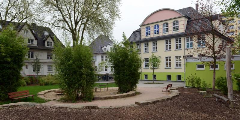 Außengelände der Kita mit Spielgerüst und das schöne Gebäude im Hintergrund