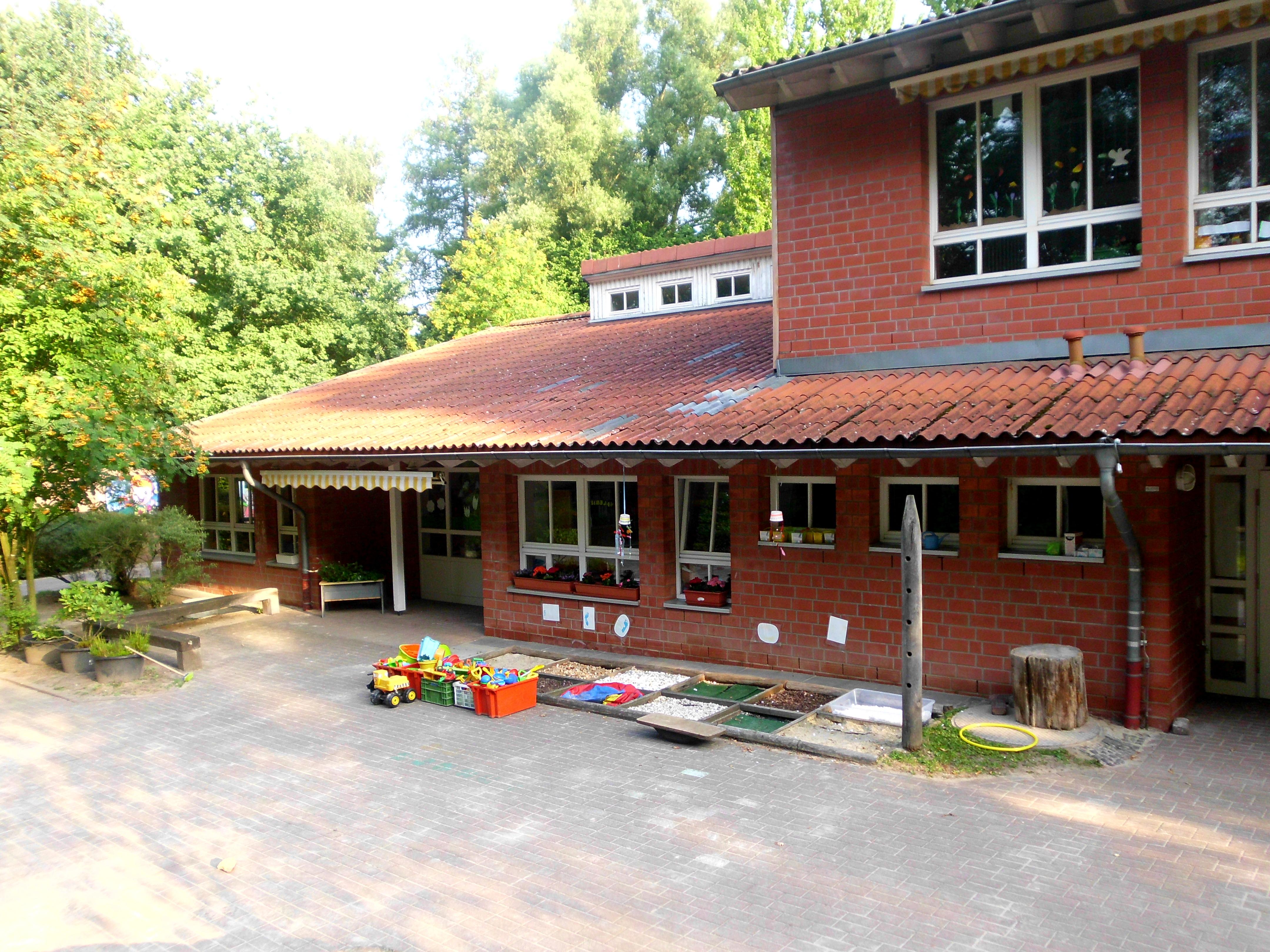 Eingangsbereich zum Außengelände mit Spielkisten vor der Tür