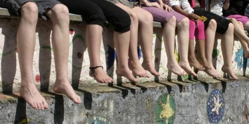 Füße von vielen Kindern, die auf einer Mauer sitzen