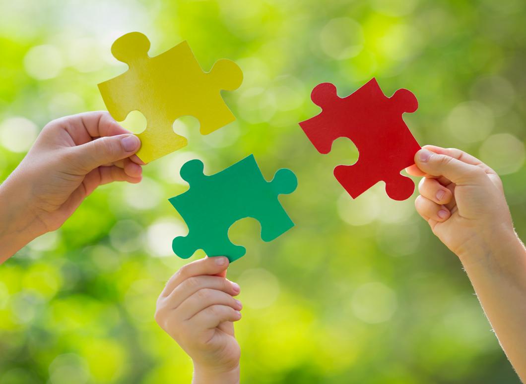 Foto: Drei Hände halten farbige Puzzleteile vor grünes Laubwerk