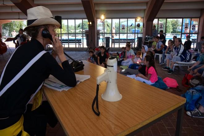 Im Vordergrund sitzt eine Frau mit Hut an einem Schreibtisch sie hält sich einen Telefonhörer ans Ohr. Auf dem Tisch steht ein Megafon. Im Hintergund sitzen Kinder.
