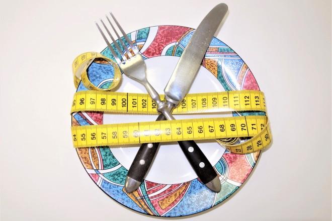 Abbildung eines Tellers mit Messer und Gabel, die von einem Maßband eingewickelt sind