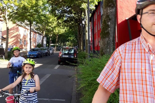 Foto einer Fahrradstrasse, im Hintergrund sind Kinder mit Fahrrädern und im Vordergrund ein Erwachsener zu sehen.