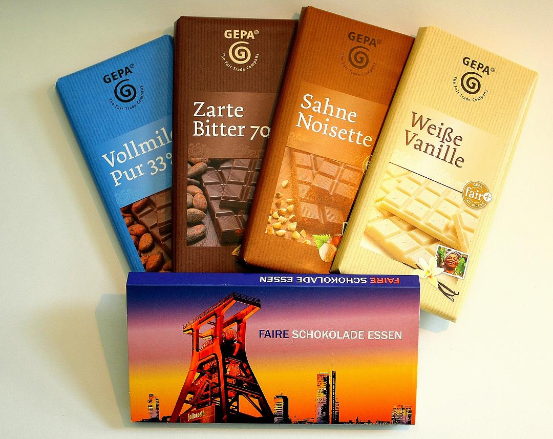 Foto: Vier verschiedene Tafeln Schokolade mit der Aufschrift 'GEPA The Fair Trdae Company' sowie eine Geschenk-Papp-Schuber mit dem Doppelbock der Zeche Zollverein und der Aufschrift 'FAIRE SCHOKOLADE ESSEN'