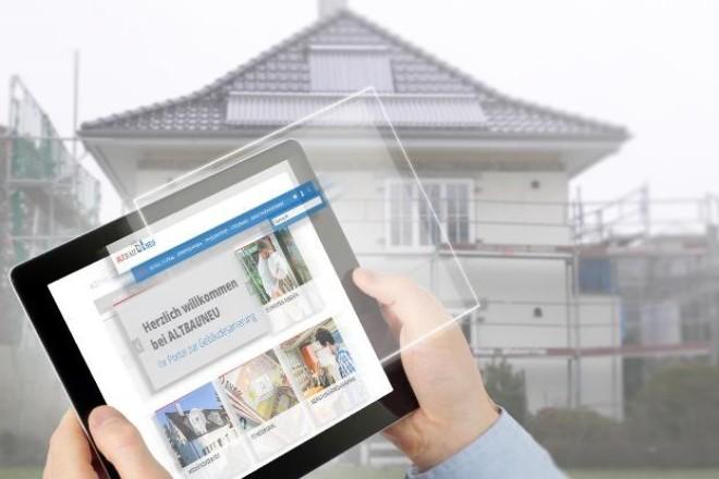 Foto: Eine Hand hält ein Tablet, auf dem ein Haus sowie der Schriftzug 'AltBauNeu' zu sehen ist. Dahinter ist eben dieses Haus nocheinmal zu sehen.