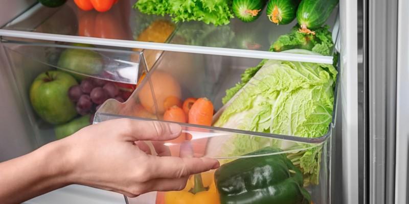 Foto: Nahaufnahme der Hände einer Person, die das Gemüsefach im Kühlschrank öffnet. Der Kühlschrank ist voll mit Obst und Gemüse.