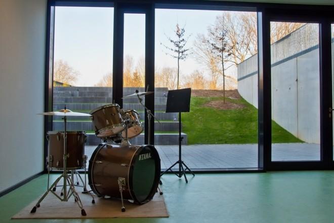 Foto: Innenansicht eines Fachraum für Musik des Erweiterungsneubaus Gymnasium Essen-Überruhr mit Blick auf das Atrium im Aussenbereich. Im Raum steht ein Schlagzeug und ein Notenständer.