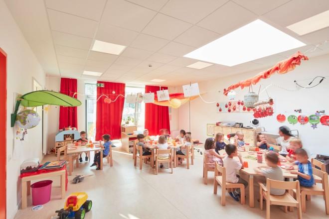 Innenaufnahme eines Gruppenraumes der neuen Kindertagesstätte. Kinder und eine Erzieherin sitzen an Tischen und frühstücken.