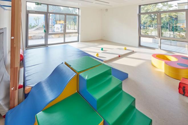 Innenaufnahme des Mehrzweckraumes der neuen Kindertagesstätte. Der Raum kann für Sport und Spiel aber auch als Veranstaltungsraum genutzt werden. Das Bild zeigt den Raum mit blauer Gymnastikmatte, einem Klettergerüst, Bällen sowie eine Spiellandschaft zum Sitzen, Klettern oder Bauen.