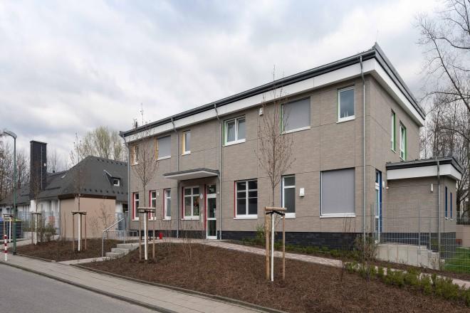 Foto: Fassadenansicht des zweigeschossigen Neubaus der Kindertagesstätte an der Stauderstraße von Westen. Links neben dem Neubau schließt sich die bestehende Kita an.