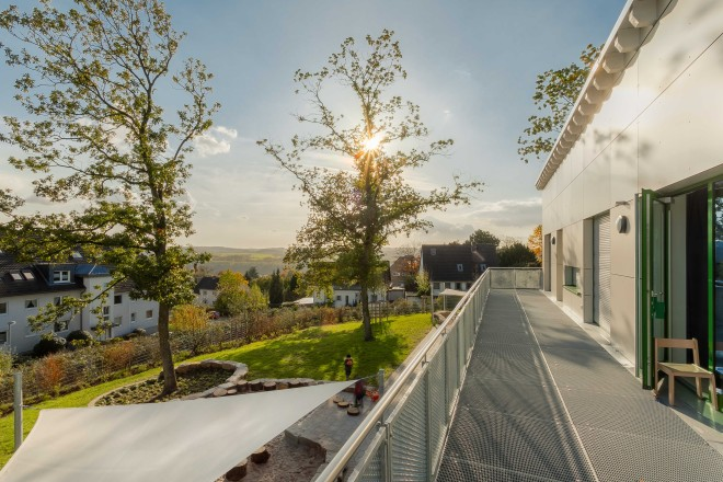 Foto: Blick vom Balkon der KiTa Katthult in südwestliche Richtung. Das Bild zeigt rechts den Balkon und das Obergeschoss des Gebäudes, links den Außenbereich der Kita sowie die Umgebungsgebäude und einen weiten Blick in die Landschaft.
