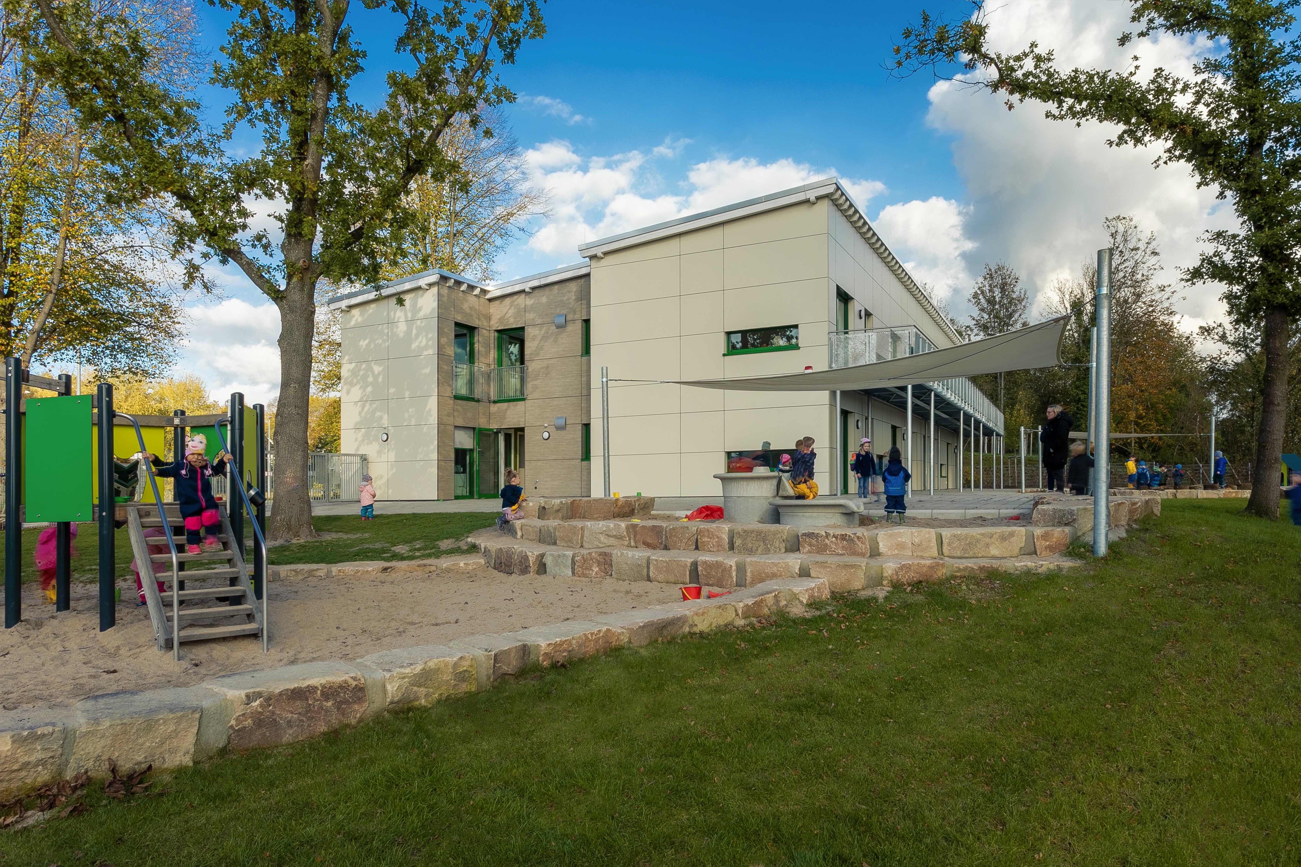 Foto: Ansicht des Neubaus der KiTa Katthult aus Westen. Das Bild zeigt den zweigeschossigen Neubau. Vor dem Gebäude liegt ein Sandspielplatz mit Spielgeräten und einem durch Sonnensegel überdachten Außenbereich der von spielenden Kindern genutzt wird.