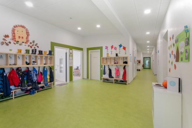 Foto: Innenansicht des Flurs im 1. Obergeschoss der Kita Katthult. Das Bild zeigt Garderoben mit Kinderkleidung und herbstliche Dekorationen im Flur. Der Flurboden und die Umrahmungen der Türen zu den Gruppenräumen sind in grüner Farbe angelegt.
