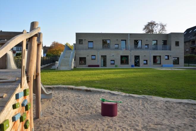 Foto: Fassadenansicht der Gartenseite der Kita Lohstraße mit Spielfläche im Vordergrund