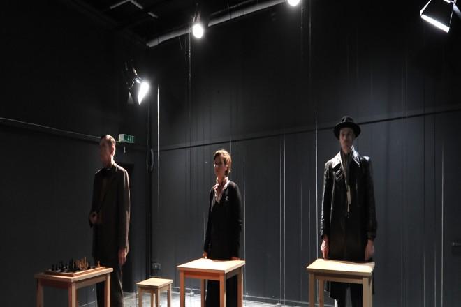 """Foto: Szene aus dem Theaterstück """"Kopenhagen"""" von Michael Fraynder, Studio-Bühne Kopenhagen. Eine Schauspielerin steht zwischen zwei Schauspieler auf der Theaterbühne im Bühnenlicht hinter Stehtischen."""
