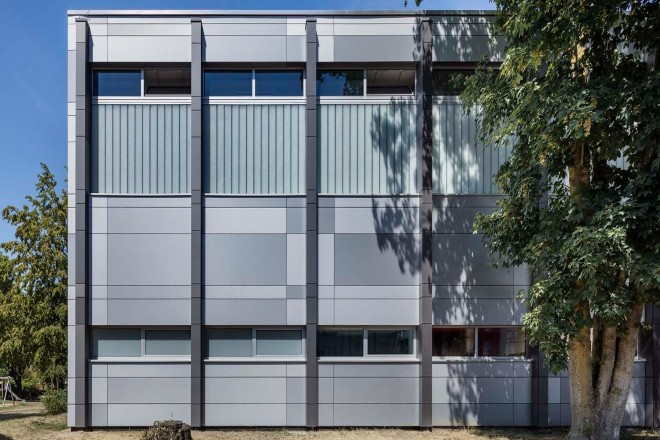 Foto: Ansicht der neugestalteten Fassade der Sporthalle Beisingstraße von Osten. Die Fassade zeichnet sich durch verschieden graugefärbte Hartfaserplatten, horizontal verlaufende Fensterbänder sowie vertikal hervorstehende Tragwerksstützen aus.